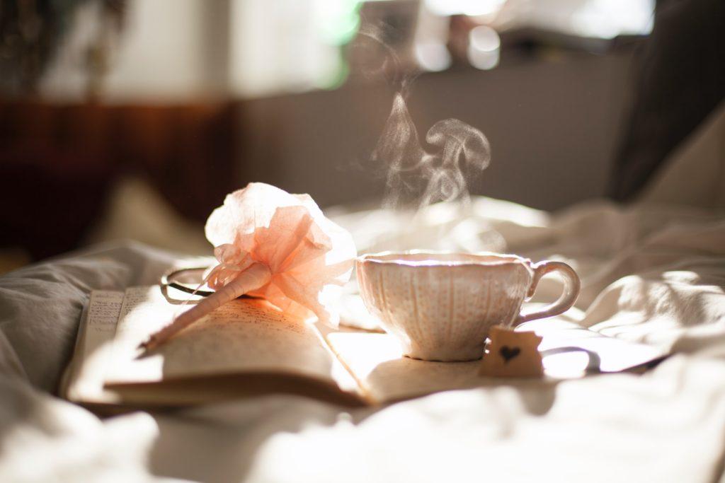 本と湯気がでているティーカップ